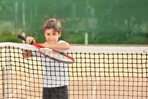 Cute little boy with tennis racket on court