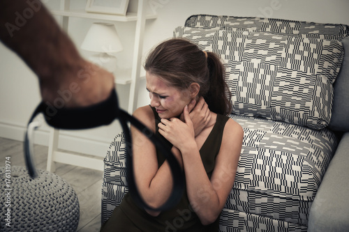Fotografiet  Young woman subjecting to violence in room