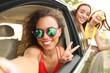 Beautiful young women looking out of open car window