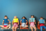 Fototapeta Kuchnia - Cute little children reading books while sitting near color wall