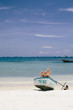 Couple lying in boat on the tropical beach