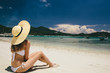 Woman dressed in bikini and wide-brimmed sunhat relaxing on the beach