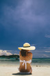 Woman dressed in bikini and wide-brimmed sunhat sitting on the beach