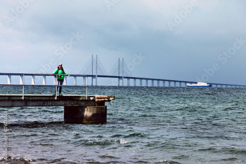 Happy woman tourist posing on the Oresund Bridge background. Poster