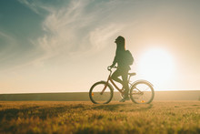 Silhouette Of Beautiful Woman Girl Riding Bicycle On Grass Lawn At Sunset Sunrise