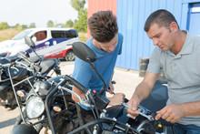 Men Checking Motorbike At An I...