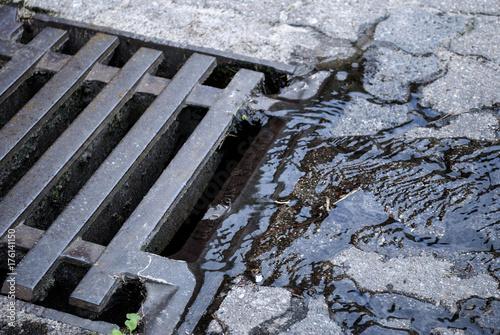 Fotografie, Obraz  Wasser / Regenwasser fliesst in Kanal Deckel