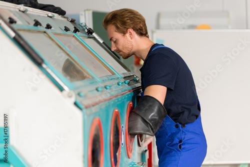 Fényképezés Worker operating a sandblast machine in a metal workshop