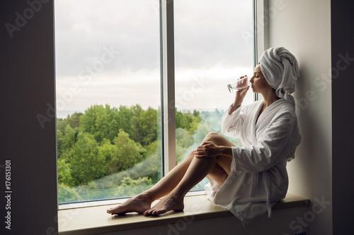 Fotografie, Obraz  girl in a bathrobe and towel on head sitting