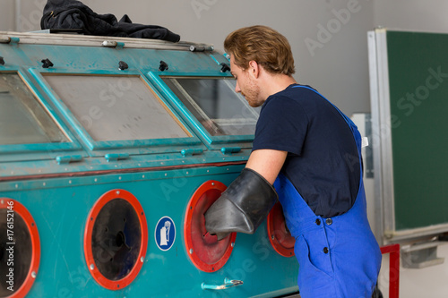 Worker operating a sandblast machine in a metal workshop Tapéta, Fotótapéta