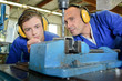 Engineer with apprentice using bench drill