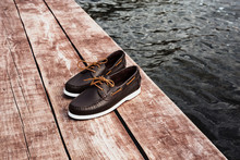 Brown Leather Men's Top Sider Shoes Or Boat Shoes With White Sole On A Brown Wooden Pier Or On A Brown Wooden Boards Near The Water, Or Rivers, Or Lakes, Or The Sea. Fashion Advertising Shoes Photos.