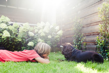 Boy Lying In The Grass In The Garden With His Dog