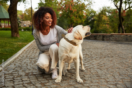 Fotografía  Young smiling lady in casual clothes sitting and hugging dog in park