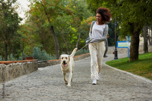 Funny healthy lady running in the morning with her dog in park