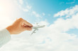 hand holding airplane model in front of cloudy blue sky background. air transportation concept.