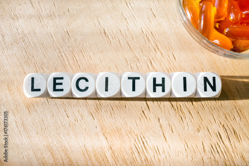 Lecithin gel pills in a round glass bowl and with the word Lecetin from the letters of cubes on a light wooden background Fototapet