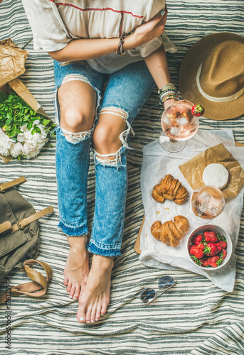 Keuken foto achterwand Picknick French style romantic picnic setting. Woman in denim pants sits with glass of ice rose wine, strawberries, croissants, brie cheese, hat, sunglasses, peony flowers, top view. Outdoor gathering concept