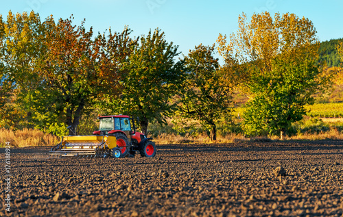 Fényképezés  Farmer with tractor seeding - sowing crops at agricultural fields in autumn