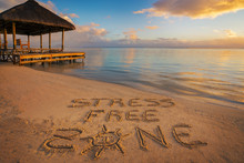 """Foreground Written In The Sand """"stress Free Zone"""" At Sunset In Mauritius Island With Jetty Silhouette And Fishermen's Boats In The Background."""