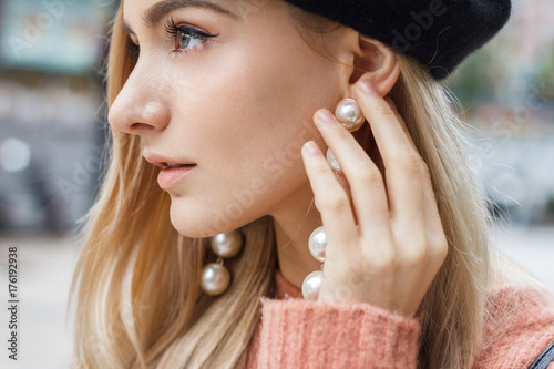 Close up detail of beautiful young blonde woman dressed in pink sweater with gorgeous earrings made of big pearls.