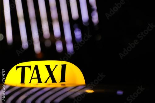 Zdjęcie XXL Rozjarzony taxi znak na dachu samochód w świetle świateł nocy miasto.