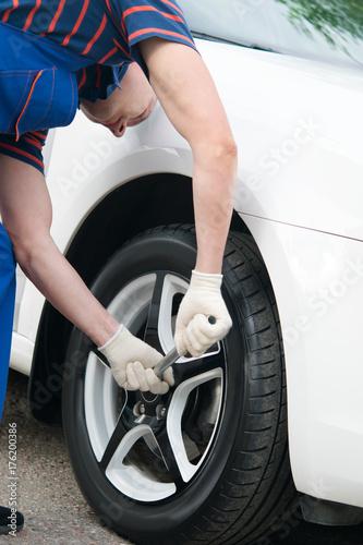 Zdjęcie XXL Mechanik sprawdza mocowanie kół do samochodu