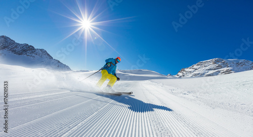 Garden Poster Winter sports Young man skier running down the slope in Alpine mountains
