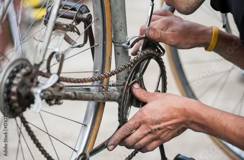Fototapeta Mechanik naprawia łańcuch zabytkowego roweru