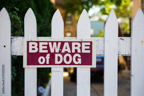 Photo Beware of dog sign on white picket fence