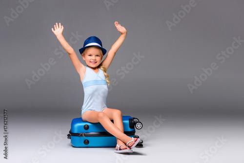 Fotobehang School de yoga child in swimsuit sitting on suitcase