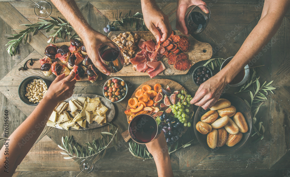 Fototapety, obrazy: Flat-lay of friends eating and drinking together. Top view of people having party, gathering, celebrating at wooden rustic table set with various wine snacks and fingerfoods. Hands holding glasses