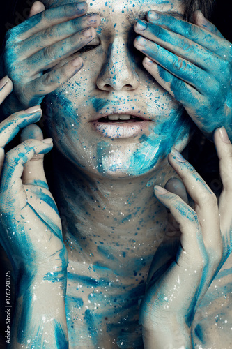 Beautiful model with creative makeup art. Caucasian girl with painted face in blue white flowers