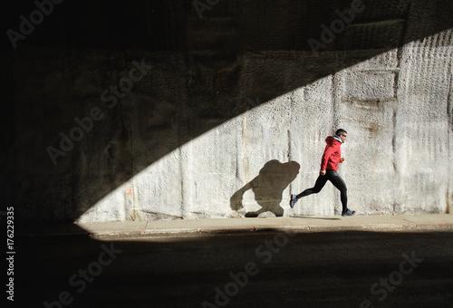 Plakat Potężny sportowiec bieganie i bieganie. Szkolenie człowieka i rzucając cień w ścianę.