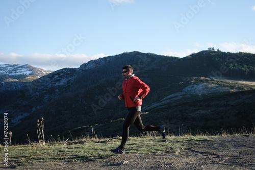 Plakat Sporty mężczyzna działający krzyż kraju plenerowy na górze. Trening sportowca i ćwiczenia w późnej zimie.