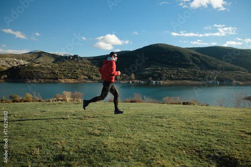 Plakat Sporty mężczyzna biegać plenerowy na górze. Trening sportowca i ćwiczenia w późnej zimie.