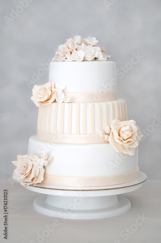 Plakat Trójwarstwowy biały ślubny tort dekorujący z kwiatami od mastyksu na białym drewnianym stole. Obraz menu lub katalogu słodyczy. Widok z góry.