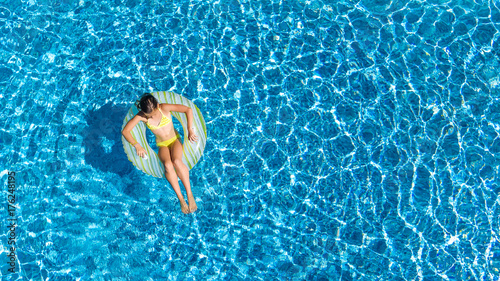 Photo  Aerial view of girl in swimming pool from above, kid swim on inflatable ring don
