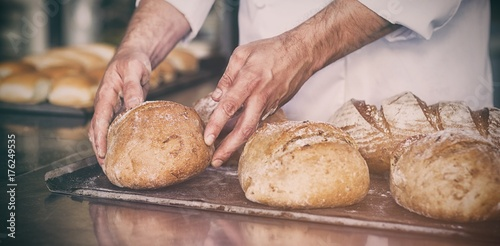 Foto op Aluminium Brood Baker checking freshly baked bread