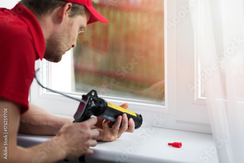 Obraz worker applying silicone sealant under window frame - fototapety do salonu
