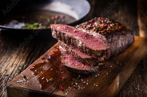 Garden Poster Steakhouse Beef steak. Juicy medium Rib Eye steak slices on wooden board with fork and knife herbs spices and salt