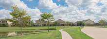 Walking Pathway Alongside Leads To Residential Houses By The Lake In Pearland, Texas, USA. Panorama Style.