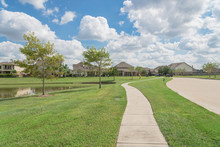 Walking Pathway Alongside Leads To Residential Houses By The Lake In Pearland, Texas, USA.