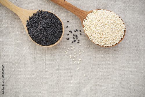 Black and white sesame on wood spoon background with space