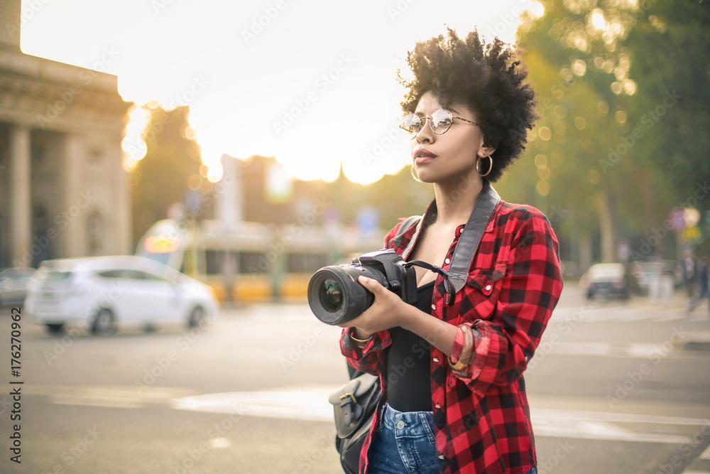 Fototapety, obrazy: Beautiful woman taking photos in a city