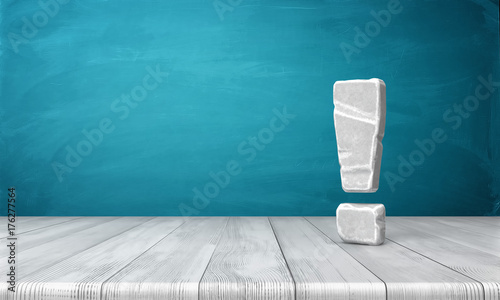 Fotografie, Obraz  3d rendering of a grey-white exclamation mark made of stone standing on a wooden surface in front of blue background