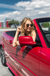 Blonde beautiful woman in sunglasses sitting in red car by the sea. Vacation concept. Happyness. Freedom. Road trip on beautiful sunny summer day