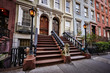 a row of colorful brownstone buildings