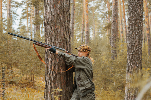 Foto op Aluminium Jacht Woman hunter in the woods. Autumn hunting season. Outdoor sports.