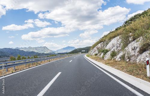 Fototapeta Szybka wiejska droga wśród gór.